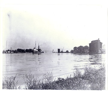 Fr. Edward J. Dowling, S.J. Marine Historical Collection: Port bow view, entering Port Dalhousie, Ont. in the early 1900s. Note the lighthouse on the pier, grain elevator, and the coal dumper for fuel and cargo.