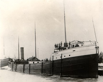"""Iosco - Starboard bow view looking aft, note crew and passengers. Poles along the hull are called """"fenders"""", they keep the ship's wooden hull from scraping on docks and lock walls."""
